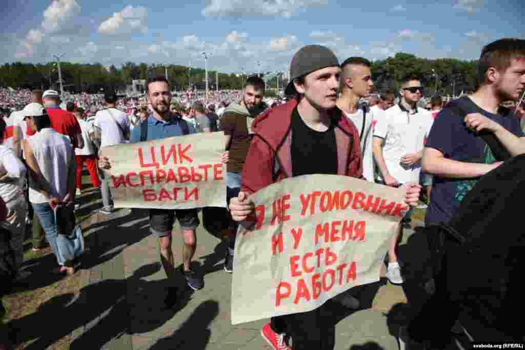 Молодий чоловік (праворуч) тримає у руках плакат:«Я не злочинець, у мене є робота». Цей плакат – посилання на промову Олександра Лукашенка 12 серпня під час чергового засідання президента з правоохоронцями та представниками інших державних структур.«Основа всіх цих так званих протестувальників – люди із кримінальним минулим, сьогоднішні безробітні. Немає роботи, значить, «гуляй дядько по вулицях і проспектах». Тому я по-доброму прошу і попереджаю всіх: влаштуватися на роботу тим, хто не працює», – заявив тоді Лукашенко