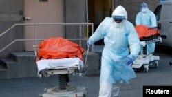 Нью-Йорктегі клиникада вирустан қайтыс болған адамның денесін мәйітханаға апара жатқан медицина қызметкері. 4 сәуір 2020 жыл.