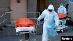 Медики выносят на каталках тела погибших от COVID-19 пациентов из клиники Wyckoff Heights в Нью-Йорке. 4 апреля 2020 года.