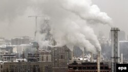 Exhaust fumes from a gas-powered heating plant rise in the air over Kyiv.