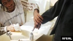 An Afghan man inks his finger while voting in the first round of the presidential election. Can he be convinced to vote again?