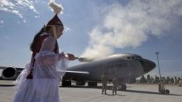 Женщина во время традиционного ритуала перед открытием новой инфраструктуры на американской авиабазе Манас. Бишкек, 23 июня 2011 года.