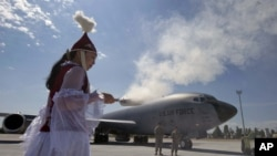 АҚШ әскерилері орналасқан Манас әуе базасындағы жаңа инфрақұрылымның ашылу шарасында тұрған ұлттық киім киген қыз. Бішкек, 23 маусым 2011 жыл. Көрнекі сурет.