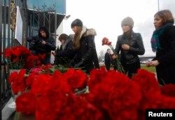 Люди приносят цветы в память о погибших к зданию аэропорта Казани