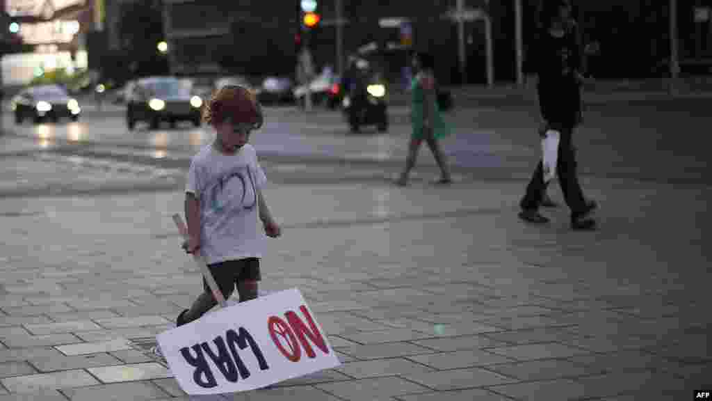 An Israeli child holds a sign during a demonstration on August 23 in the coastal city of Tel Aviv against a possible Israeli military strike on Iran. (AFP/David Buimovitch)
