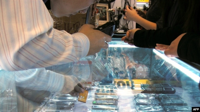 China -- A vendor sells various 'high imitation' iPhones at a shop in Beijing, 28Oct2009