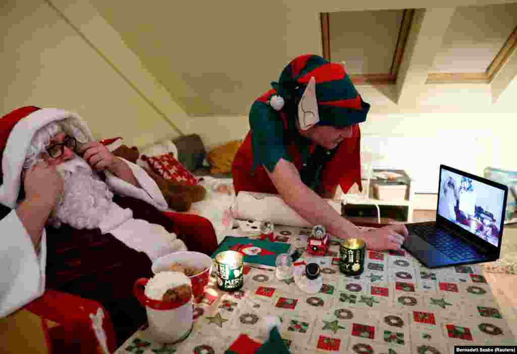 Ассистент помогает Палу Пиллмайеру, одетому как Санта-Клаус, готовиться к общению с детьми с помощью видеочата. Венгрия, 30 ноября 2020 года