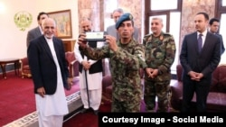 Essa Khan (center) was given a new apartment for his actions by Afghan President Ashraf Ghani (left).