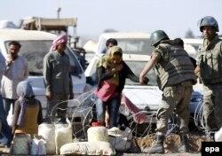 Турецкие солдаты помогают сирийским беженцам