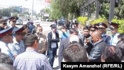Полицейские разговаривают с людьми, пытающимися пройти на оцепленную площадь Республики. Алматы, 21 мая 2016 года.