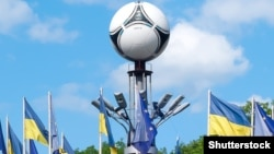 Ukraine – National flags and Adidas tango 12, the official matchball of UEFA EURO 2012 on European Square. Kyiv
