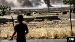 Мальчик в турецком городке Каркамыш на фоне дыма, вьющегося над сирийским пограничным городом Джераблусом, 1 сентября 2016 года.