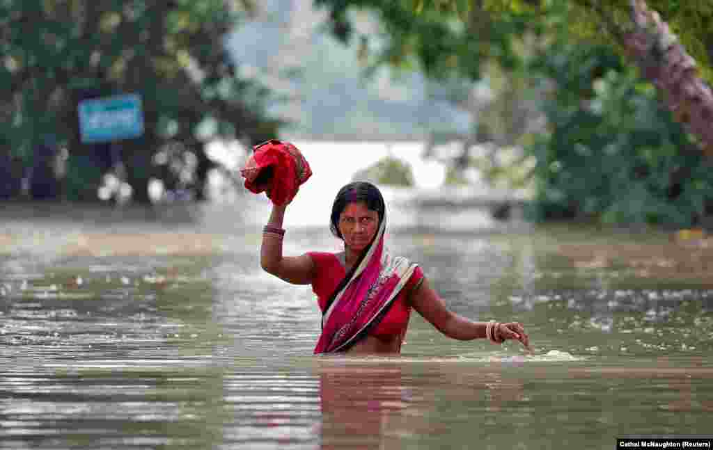 A woman wades through a flooded village in the eastern state of Bihar, India. (Reuters/Cathal McNaughton)