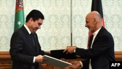 Afghanistan -- Afghan President Ashraf Ghani (R) exchanges documents with Turkmen President Gurbanguly Berdymukhammedov at the Presidential Palace in Kabul, August 27, 2015