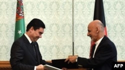 Afghan President Ashraf Ghani (R) exchanges documents with Turkmen President Gurbanguly Berdymukhamedov at the Presidential Palace in Kabul, in August.