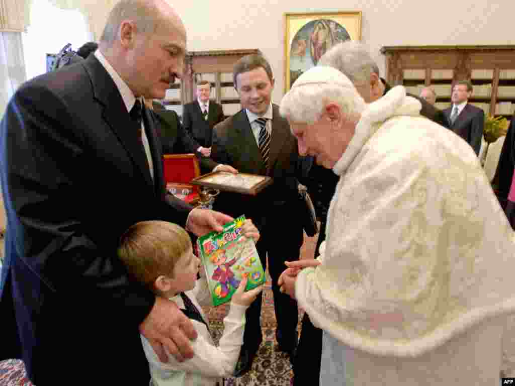 Mykalay, son of Belarusian President Alyaksandr Lukashenka (left), offers a book to Pope Benedict during their meeting in the Vatican in April 2009.