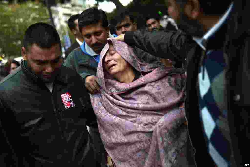 The mother of a 27-year-old Pakistani man stabbed to death reacts as she leaves an Athens court where two suspected members of the Greek neo-Nazi party, Golden Dawn, accused of her son's murder, were scehduled to receive a verdict on December 18. (AFP/Aris Messinis)