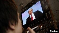 Дондогу Ростов шаарынын тургундары Владимир Путиндин сөзүн кафеде сыналгы аркылуу угууда. 2010-жылдын 16-декабры.