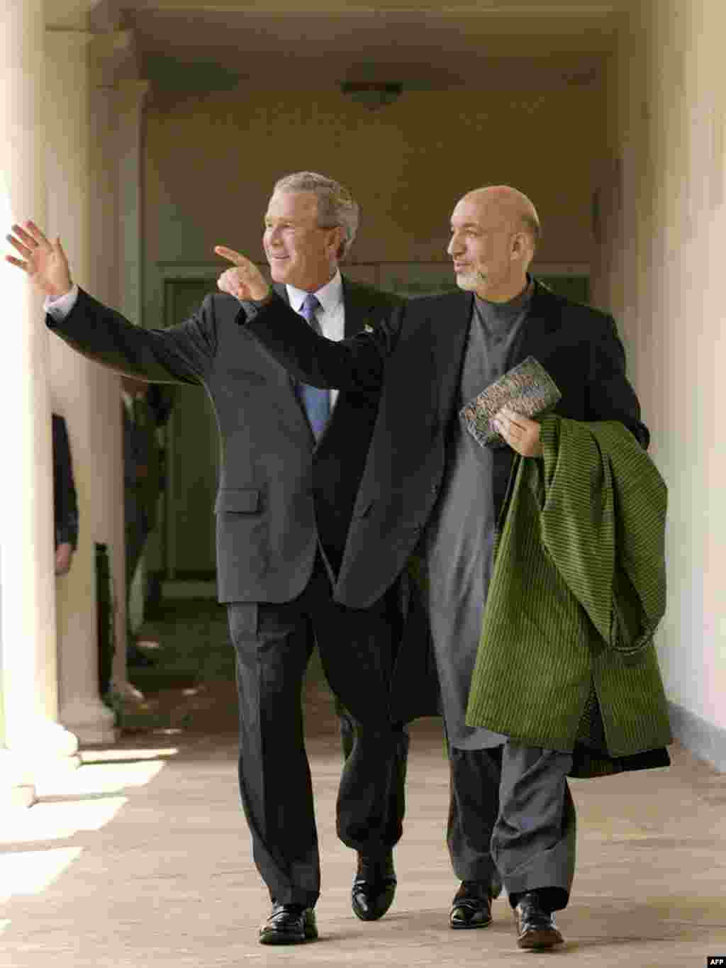Afghanistan and Karzai - U.S. President George W. Bush (left) walks with Afghan President Hamid Karzai after speaking to reporters in the Rose Garden at the White House on June 15, 2004, in Washington, D.C.