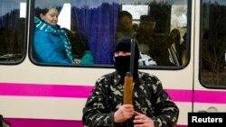 Вооруженный человек в маске рядом с пассажирским автобусом на блокпосту на дороге из Симферополя в Севастополь. 13 марта 2014 года.