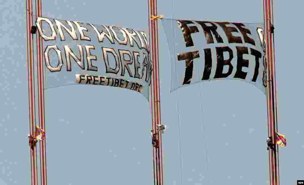 """Трое демонстрантов развернули баннер """"Освободите Тибет"""" на пути следования эстафеты на мосту Золотые Ворота в Сан-Франциско, 2008."""