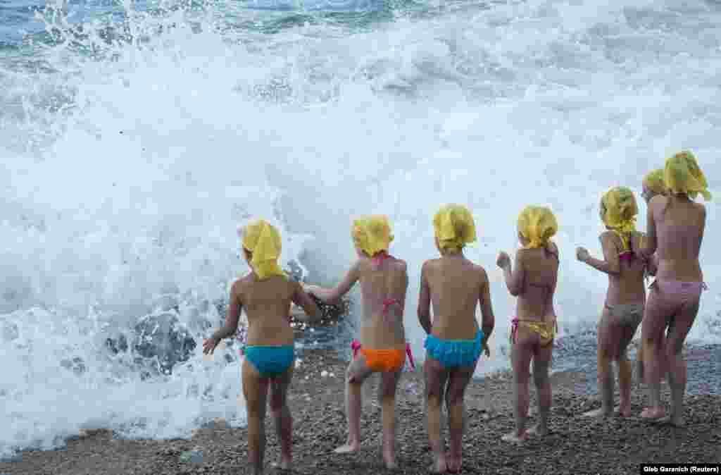 Children play at a beach in the rain near the Crimean village of Berehove on the Black Sea. (Reuters/Gleb Garanich)