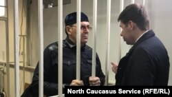 Oyub Titiyev (left) in the defendant's cage in a Chechen court on March 11