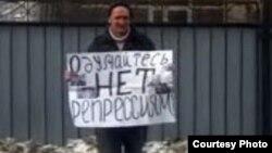 """Активист незарегистрированной оппозиционной партии """"Алга"""" Владимир Казначеев проводит пикет у здания ДКНБ. Алматы, 14 февраля 2012 года."""