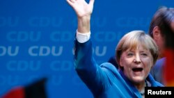 German Chancellor Angela Merkel waves to supporters as she celebrates after the first exit polls at party headquarters in Berlin on September 22.