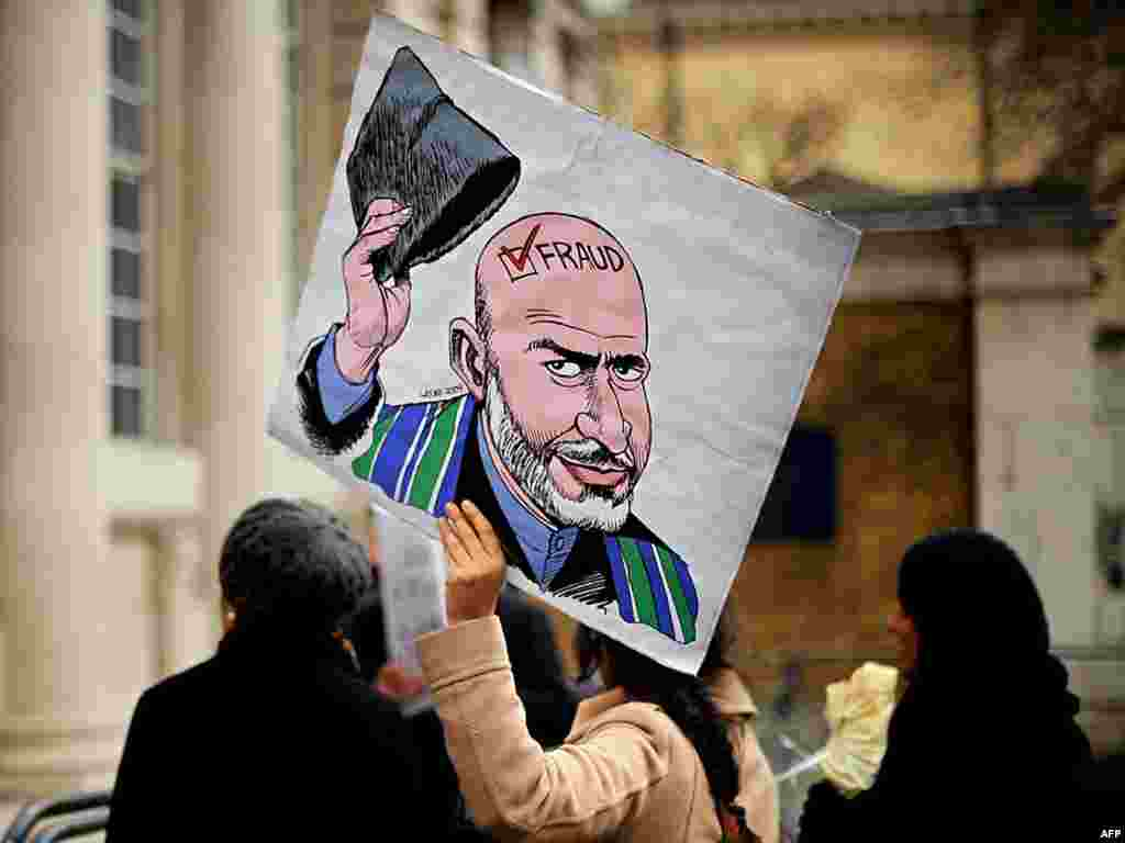 A protester holds a satirical cartoon of Afghan President Hamid Karzai outside the London Conference on Afghanistan. - Britain hosted a conference on January 28 to discuss handing security responsibilities to local Afghan forces and how to win over former Taliban members. Photo by Ben Stansall for AFP