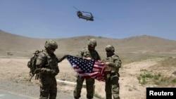 Солдаты НАТО раскрывают американский флаг. Кабул, 18 июня 2013 года.