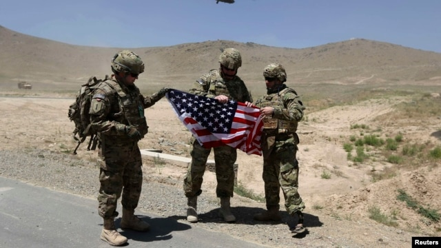 NATO soldiers stand with a U.S. flag after a security handover ceremony at a military academy outside Kabul in June.