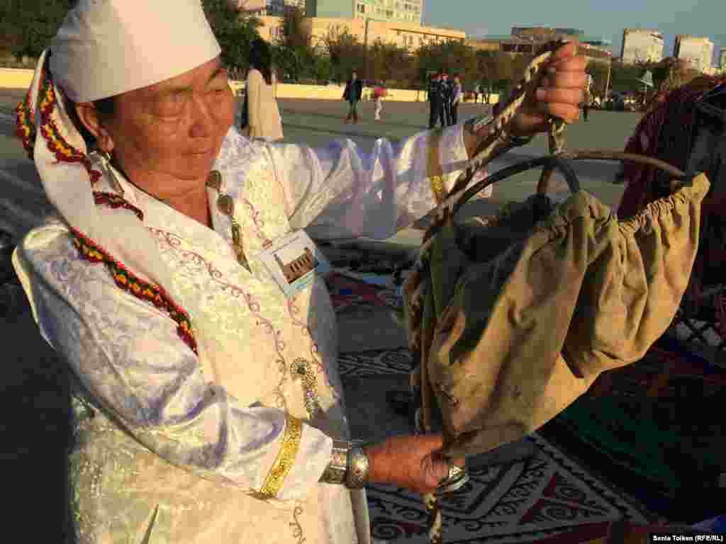 Мастерица из города Жанаозен Гульнар Жакиева показывает, каким кожаным сосудом раньше набирали воду из колодца.