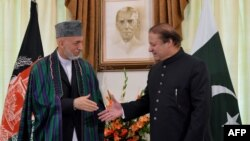 Pakistani Prime Minister Nawaz Sharif (right) greets Afghan President Hamid Karzai in Islamabad on August 26.