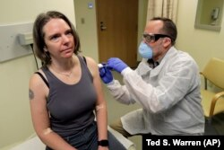 A U.S. pharmacist gives a test subject an injection in a first-stage safety-study clinical trial of a potential vaccine for COVID-19 in Washington.