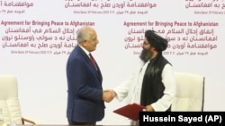 U.S. peace envoy Zalmay Khalilzad, left, and Mullah Abdul Ghani Baradar, the Taliban group's top political leader, shake hands after signing a peace agreement between Taliban and U.S. officials in Doha on February 29.