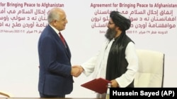 U.S. envoy Zalmay Khalilzad (left) and Mullah Abdul Ghani Baradar, the Taliban's top political leader, shake hands after signing a peace agreement in Doha on February 29.