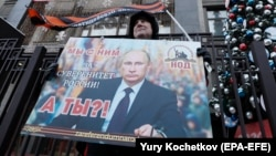 An activist from a pro-Kremlin movement holds a placard with a portrait of Russian President Vladimir Putin in front of the State Duma in Moscow on January 23.
