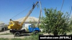 Türkmenistanda elektrik edaranyň işgärleri elektrik geçiriji liniýalary bejerýärler. Arhiwden alnan illýustrasiýa suraty