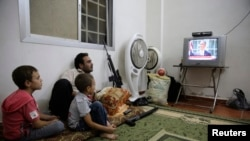 A Free Syrian Army fighter watches US President Barack Obama's speech with his family in Ghouta, Damascus, August 31, 2013