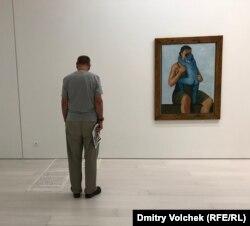 """Посетитель """"Документы"""" в Афинах перед картиной Анджея Врублевского """"Мать с убитым младенцем"""" (1949)"""