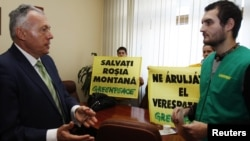 "Romanian Environment Minister Laszlo Borbely (left) talks to a Greenpeace activist while others hold banners reading ""Save Rosia Montana"" in his office in central Bucharest on January 31."