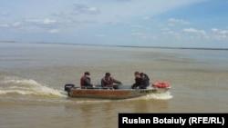 Люди на моторной лодке направляются к затопленному селу Аганас Целиноградского района Акмолинской области, 20 апреля 2015 года.