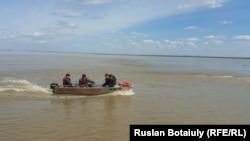 Спасатели перевозят жителей села Аганас на лодке по затопленной местности. Акмолинская область, 20 апреля 2015 года.