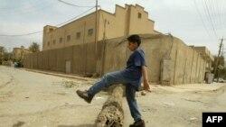 فتي يلهو أمام معبد يهودي مغلق في بغداد