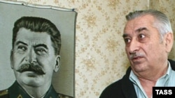 Yevgeny Dzhugashvili with a portrait of his grandfather