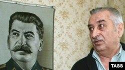 Евгений Джугашвили у портрета деда — советского вождя Иосифа Джугашвили (Сталина). Тбилиси, 4 марта 2003 года.