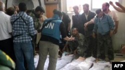 """A photo released by the Syrian opposition shows UN observers inspecting the bodies of the 92 victims, more than 30 of them young children. The UN called the deaths a """"brutal breach"""" of international law."""
