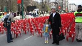 Biba Mehimovic stands with her granddaughter Sara in front of the small red chairs symbolizing the 643 children who died in the siege.