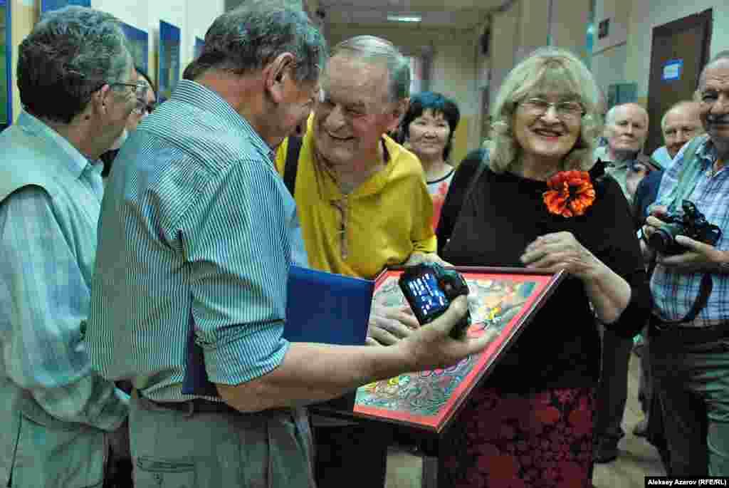 Валерия Коренчука поздравляют инженер и поэт Валентин Малышко и художница и поэтесса Лидия Коваленко. Она дарит юбиляру нарисованную ею картину.